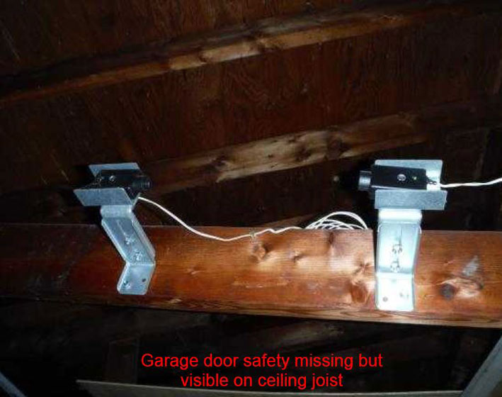 Garage door safety missing but visible on ceiling post